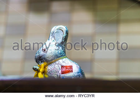 Favorina chocolate easter rabbit in a plastic paper standing on a wooden table. - Stock Image