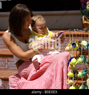 Mother and toddler shopping for colourful ceramics, Mijas Pueblo, Costa del Sol, Andalucia, Spain - Stock Image