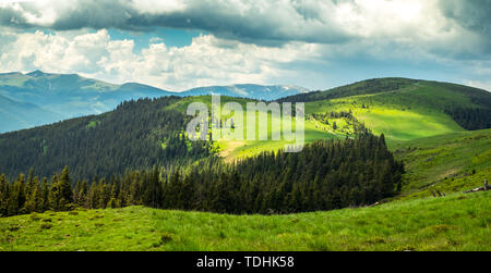 sun spots on Romanian mountains landscape with dark clouds. Cindrel mountains, Sibiu county, Romania - Stock Image