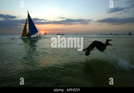A vacationer leaps into the sea along White Beach at sunset in Boracay, Philippines. - Stock Image