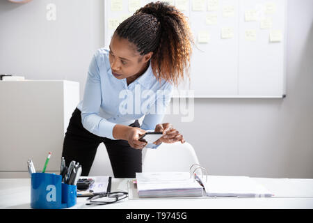 Close-up Of A Young Businesswoman's Hand Taking Photo Of Document On Mobilephone Secretly In Office - Stock Image