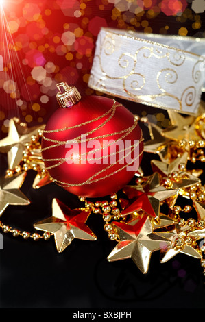 Christmas background with decorations in gold and red over black background - Stock Image