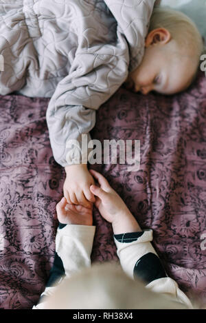 Girl holding brothers hand - Stock Image