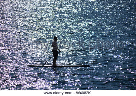 Man practicing paddle surfing with the sun shining in the water - Stock Image
