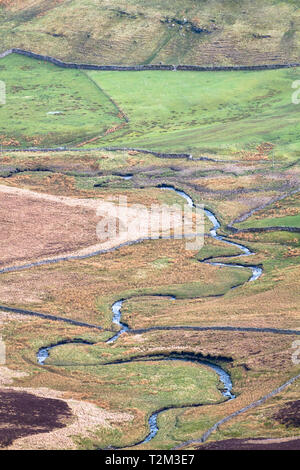 A small stream meanders through farmland in the Peak District, England. - Stock Image