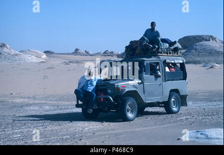 A tourist jeep in the Egyptian desert with the tour guide sat on the front bumper - Stock Image