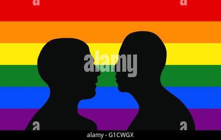 Gay couple in front of rainbow flag. - Stock Image