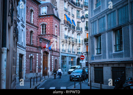 A couple walks along an elegant street in the 4th arrondissement on the Ile de la Cite in Paris France. - Stock Image