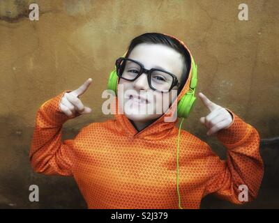 Young and happy boy with black glasses listening to music on stereo headphones - Stock Image