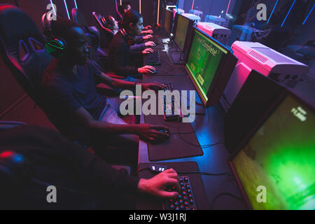 Group of concentrated young multi-ethnic people sitting on row and playing computer games online - Stock Image