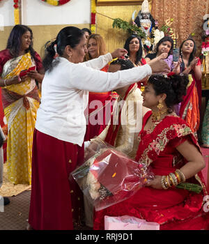 At a Hindu temple an older woman sprinkles flower petals on the heads of a bride & groom at a wedding ceremony. In Queens, New York City. - Stock Image