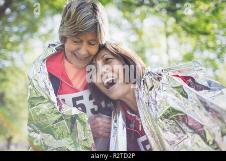 Happy active senior women friends hugging after sports race, wrapped in thermal blanket - Stock Image