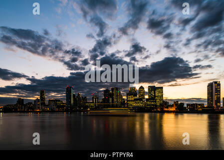 Dusk and boat trails over the River Thames and Canary Wharf, London Docklands, London, UK - Stock Image