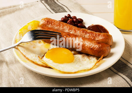 Breakfast fried eggs and sausages with orange juice - Stock Image