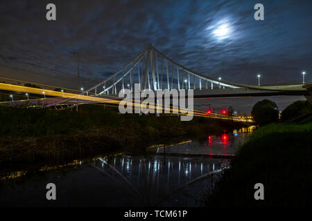 Suspension bridge at night under moonlight with light trails of moving cars and trains of highway and railway underneath - Stock Image