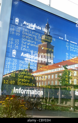 Train schedule at the Central Station in Västerås, Sweden. The ABB tower is reflected in the sign. - Stock Image