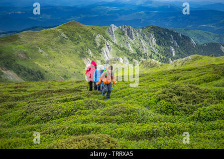 Family in a hikking day climbing up the hill - Stock Image