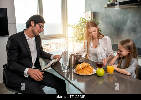Happy family have a breakfast at home - Stock Image