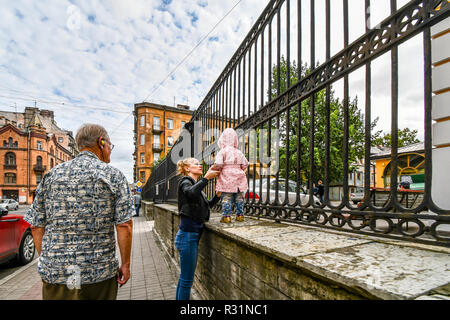 A young mother steadies her child atop a wall in the urban center of St. Petersburg, Russia. - Stock Image