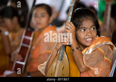 A young Filipina guitar player at an event in Mansalay, Oriental Mindoro, Philippines. - Stock Image
