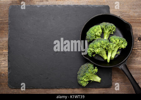 fresh broccoli in a cast iron pan  an old wooden background. view from above - Stock Image