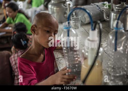 Residents of the flood hit village of Gaung Gyi use a water purifier donated by an aid agency. (Myanmar) - Stock Image