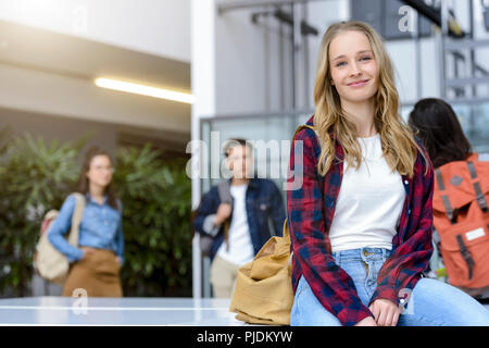 Young female university student sitting in university lobby, portrait - Stock Image