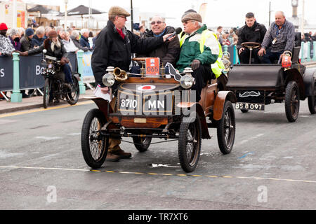 Mr Nicholas Cussons driving his 1900 New Orleans whilst a passenger is interviewed,  at the finish of the 2018 London to Brighton Veteran Car Run - Stock Image