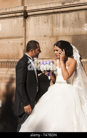 Armenia, Vagharshapat (Etchmiadzin),  Church of Saint Gayane, 7th c,  wedding couple with bride on cell phone - Stock Image