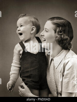 1940s LAUGHING BABY BOY TODDLER STANDING SUPPORTED BY SMILING MOTHER - b4375 HAR001 HARS 1 JUVENILE FACIAL LAUGH YOUNG ADULT BALANCE STRONG PLEASED JOY LIFESTYLE FEMALES HEALTHINESS HOME LIFE HALF-LENGTH LADIES PERSONS INSPIRATION CARING MALES EXPRESSIONS B&W HAPPINESS HEAD AND SHOULDERS CHEERFUL DISCOVERY STRENGTH EXCITEMENT BY SMILES CONNECTION JOYFUL STYLISH BABY BOY PERSONAL ATTACHMENT AFFECTION EMOTION GROWTH JUVENILES MOMS SUPPORTED TOGETHERNESS YOUNG ADULT WOMAN BLACK AND WHITE CAUCASIAN ETHNICITY HAR001 OLD FASHIONED - Stock Image