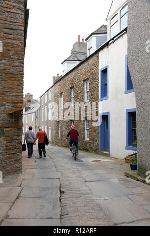 Alfred Street in Stromness, Orkney with old paving stones from a quarry in Orphir and cobble stones in the centre of the street. - Stock Image