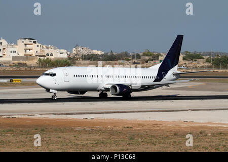 Boeing 737 commercial passenger jet plane taking off from runway. No persons visible and proprietary details deleted. Civil aviation and air travel. - Stock Image