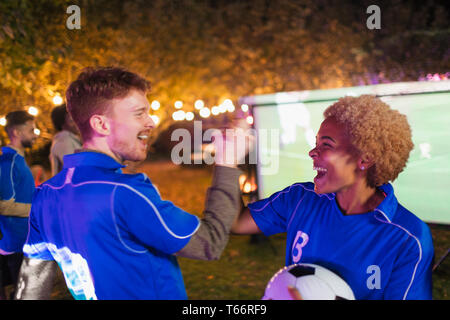 Happy friends cheering, watching soccer match on projection screen in backyard - Stock Image