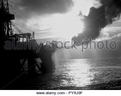 Silhouette of offshore oil platform with smoke - Stock Image