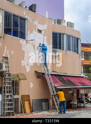 Two men one standing on a ladder working preparing a wall to be painted. - Stock Image
