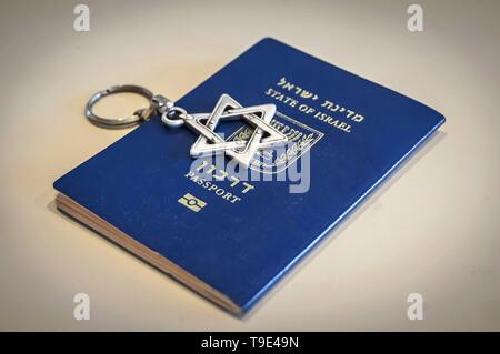 A blue passport of the State of Israel on white background with a Star of David key chain on it. Israel citizenship concept, Israeli biometric (darkon - Stock Image