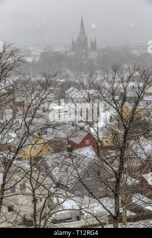 View looking over rooftops towards the church in the town of Trondheim in  Norway during a winter snow storm. - Stock Image