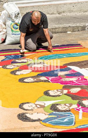 Residents create giant floral carpets made from colored sawdust and decorated with flowers during the 8th Night Celebration marking the end of the Feast of St Michael in the central Mexican town of Uriangato, Guanajuato. Every year the town decorates 5km of road with religious icons in preparation for the statue of the patron saint to be paraded through the town. Uriangato became an international sensation after wowing Brussels with their floral carpet displayed at the Brussels Grand-Place during the Belgium Floral Carpet festival. - Stock Image