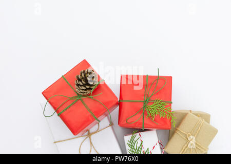 Bunch of different gift boxes wrapped in red craft paper tied with twine green ribbon pine cone juniper twig. White background. Holiday New Years corp - Stock Image