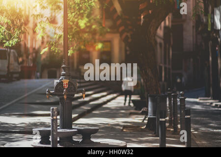 Vintage metal taps on street pole with emblem in residential district of Barcelona with a silhouette of man and - Stock Image