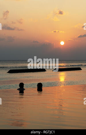 Maldives honeymoon - A honeymoon couple in the swimming pool watching the sunset, Rasdhoo atoll, the Maldives, Asia - Stock Image