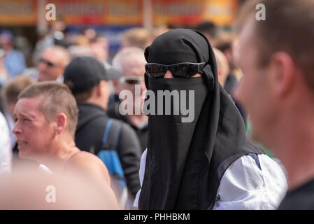 Worcester, United Kingdom. 1 September 2018. The English Defence League (EDL) held a national demonstration in the West Midlands town of Worcester, approximately 200 people attended. A counter-protest was held a short distance away with approximately 500 people.  PICTURED: An EDL supporter wearing a Niqāb and dark sunglasses in Worcester town centre. Credit: Peter Manning/Alamy Live News - Stock Image
