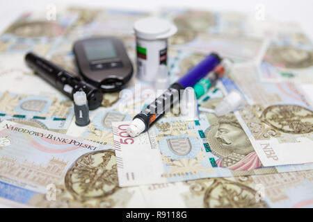 Lancet with spare needles, glucometer, strips, box of spare strips, pen injector, spare insulin and pen needles on polish money banknotes 500 PLN - Stock Image