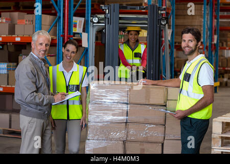 Warehouse manager and workers preparing a shipment - Stock Image