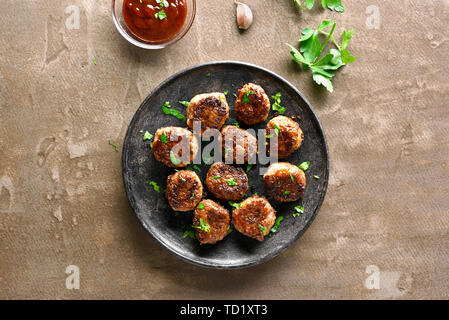Homemade cutlets from minced meat on plate over brown background. Top view, flat lay - Stock Image