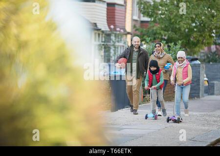 Muslim family walking and riding scooters on neighborhood sidewalk - Stock Image