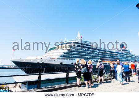 The Cunard Cruise Liner Queen Victoria berthed at the Pier Head in Liverpool, People on their lunch break admire the large passenger ship on it's arrival in Liverpool, Merseyside, England on a very sunny day. Credit: Christopher Canty Photography/Alamy Live News - Stock Image