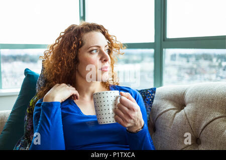Woman with red, curly hair sitting with a mug looking out the window; Surrey, British Columbia, Canada - Stock Image