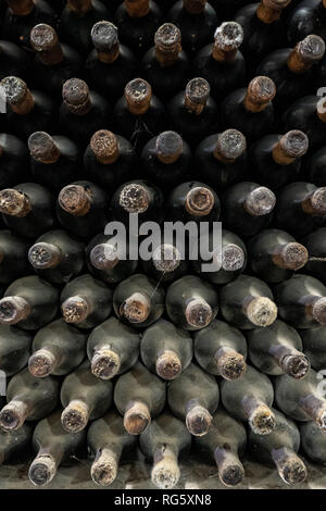 Pattern of old expensive wine bottles in winery - Stock Image