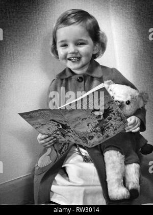 Young girl smiling as she reads her Water Baies book Circa 1945 P044490 - Stock Image